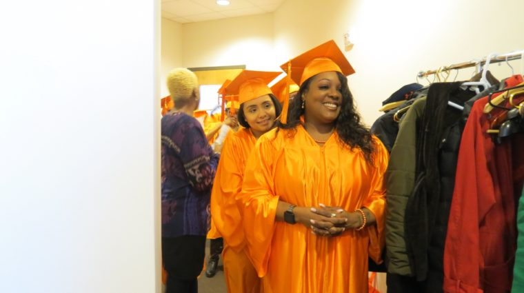 Woman in orange graduation cap and gown standing with hands folded and smiling.