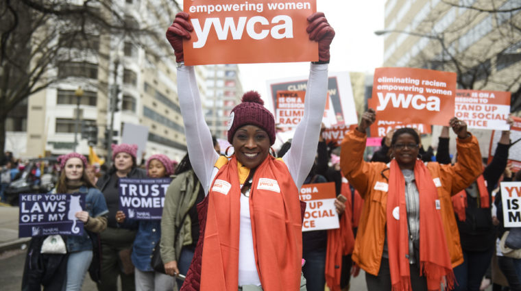 woman with orange scarf holding up sign that reads 'YWCA'